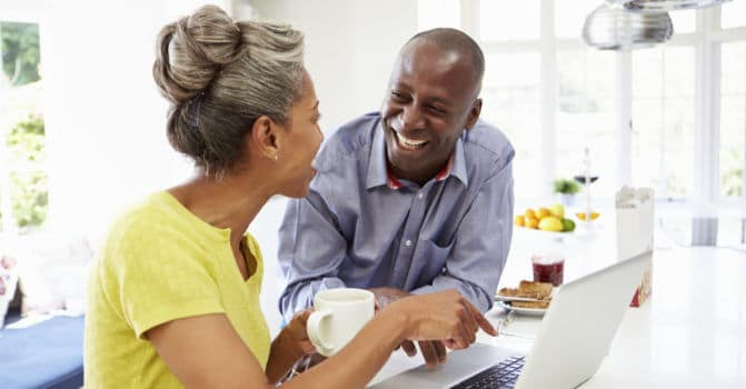 smiling middle-aged couple looking at laptop together
