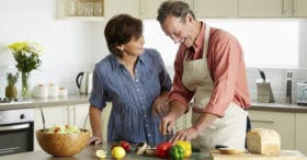 smiling middle-aged couple cooking dinner