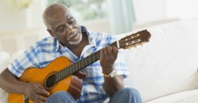 Man of Medicare age playing the guitar