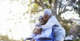 Older man in wheelchair being consoled by his wife